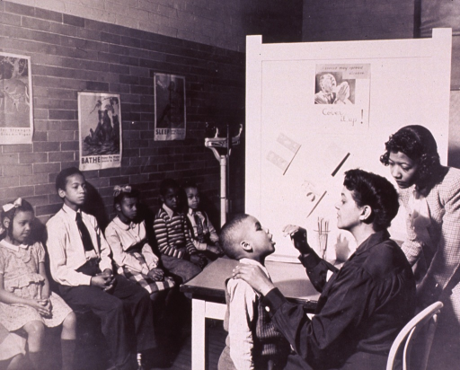 <p>Interior view of a childrens' health clinic; an African American child is having his throat examined, other children are sitting against a wall awaiting their turns.</p>