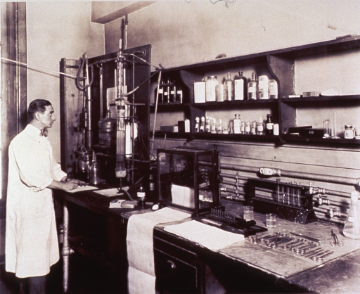 <p>A man in a long white lab coat is standing in front of laboratory equipment consisting of glass jars and tubes with metal pipes connecting.  He is writing on paper on the table on which the equipment rests.  Behind and above the table are shelves with bottles and vials.  Also on the table are test tubes in a rack, a machine in glass with printout paper coming out of it, and various types of what appear to be surgical scalpels and the like.</p>