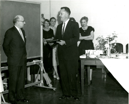 <p>National Library of Medicine Director Dr. Frank B. Rogers presents Reference Librarian Robert B. Austin with an award. Estelle Brodman stands against the wall to the right of Rogers.</p>