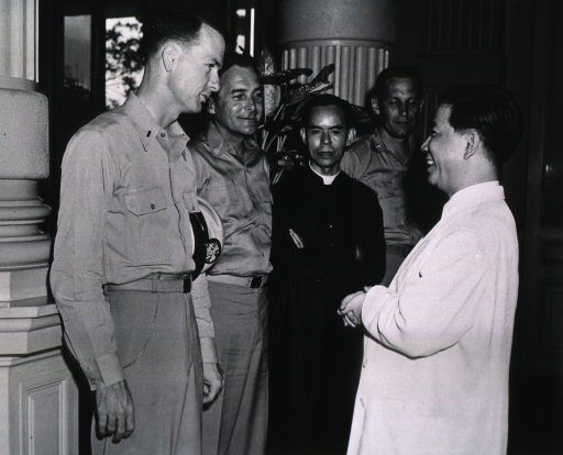 <p>Standing, right profile.  Also shown are:  Capt. Walter C. Winn, Father Khue, Major Nathan R. Smith, and President Ngo Dinh Diem of Vietnam.  Dooley, M.C. USN, is being presented &quot;Officier de L'Ordre National de Vietnam.&quot;</p>