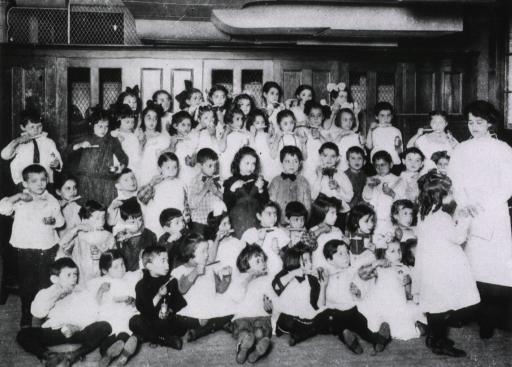 <p>Interior view: a large group of school children are gathered in a room, each is holding a toothbrush and a glass of water; a woman is standing to the right.</p>