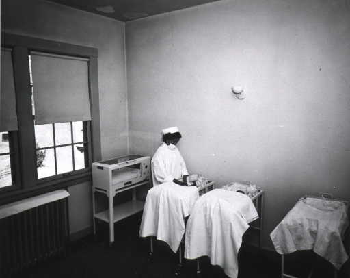 <p>An African American nurse is at the bedside of a newborn in the nursery.</p>