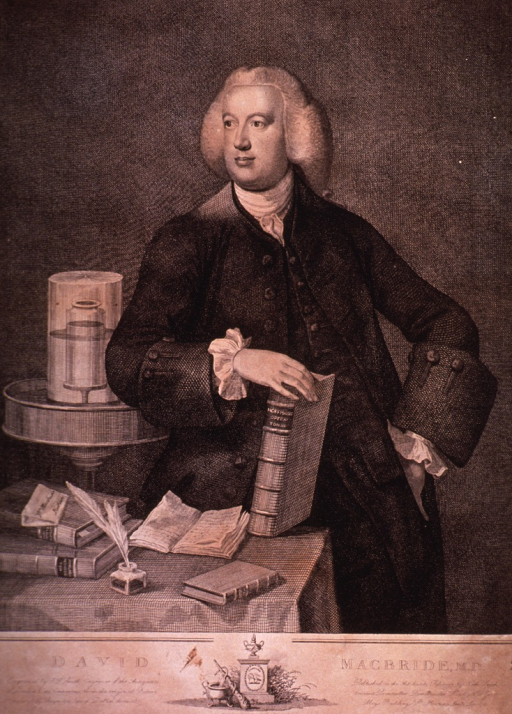 <p>Three quarter length, standing, holding a book by Hoffman on a book-laden table.</p>