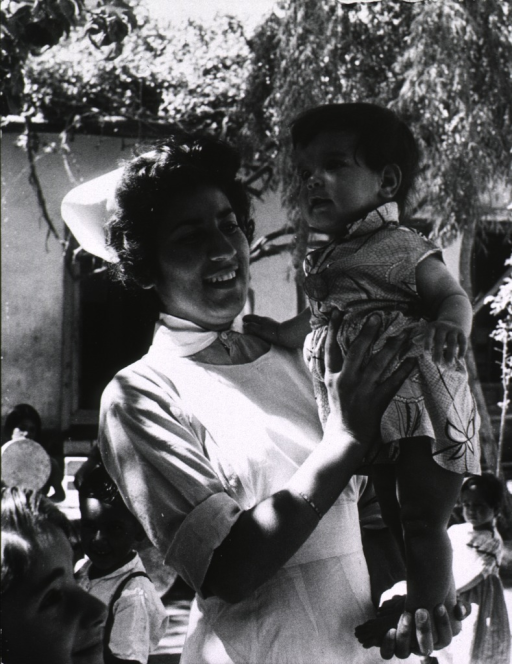 <p>Exterior view: a 17 year old auxiliary nurse midwife from Kabul is supporting a young child who is standing in the palm of her hand. Other children are seen playing in the background.</p>