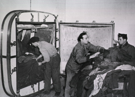 <p>Servicemen remove a pile of clothing from a wall chamber.</p>