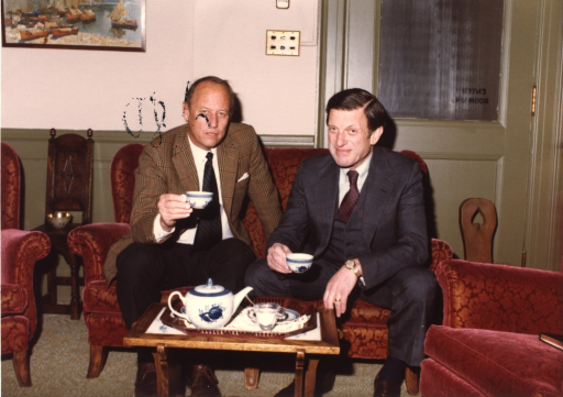 <p>Sitting in the director's office, Dr. Fredrickson, of the National Institutes of Health (NIH), and an unidentified man are holding tea cups.  A tray with a tea pot and sugar bowl is on a table in front of them.  Behind them is a door.  Under a picture of sail boats is a bowl on a wooden chair.</p>