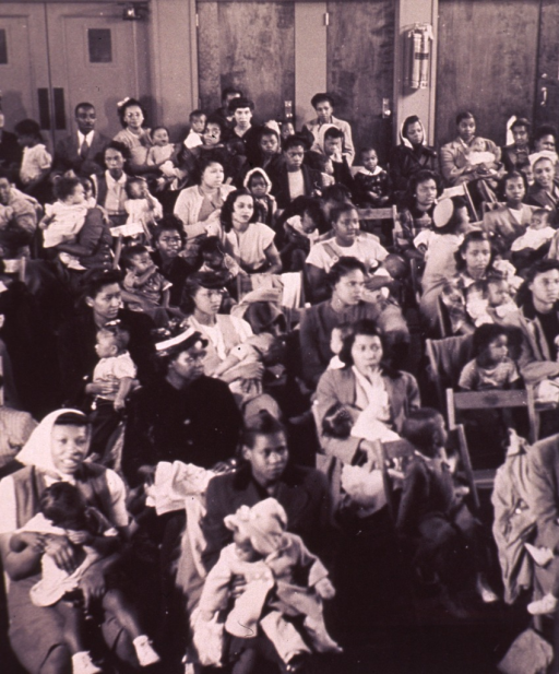 <p>Interior view of a crowded waiting room of the Herman G. Morgan Health Center in Indianapolis.  African American babies are sitting on their mother's laps and a few older children are sitting in their own chairs.</p>