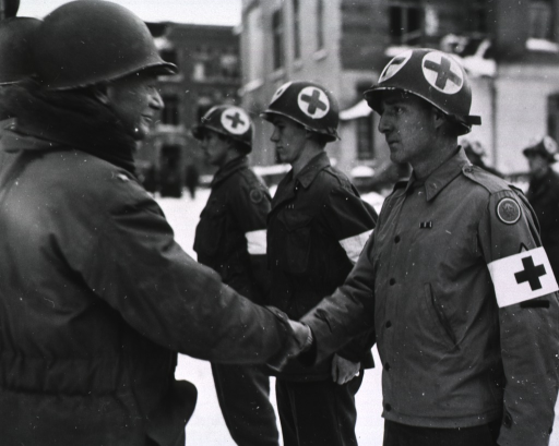 <p>Servicemen stand at attention in a row in front of a building.  It is daytime, and snow covers the ground.  Brigadier General Perrin shakes hands with one of the servicemen.</p>
