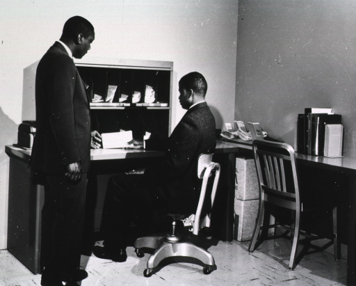 <p>Interior view: Mr. Bragg is standing next to the seated Mr. Weinstock who is holding an interlibrary loan request slip.</p>