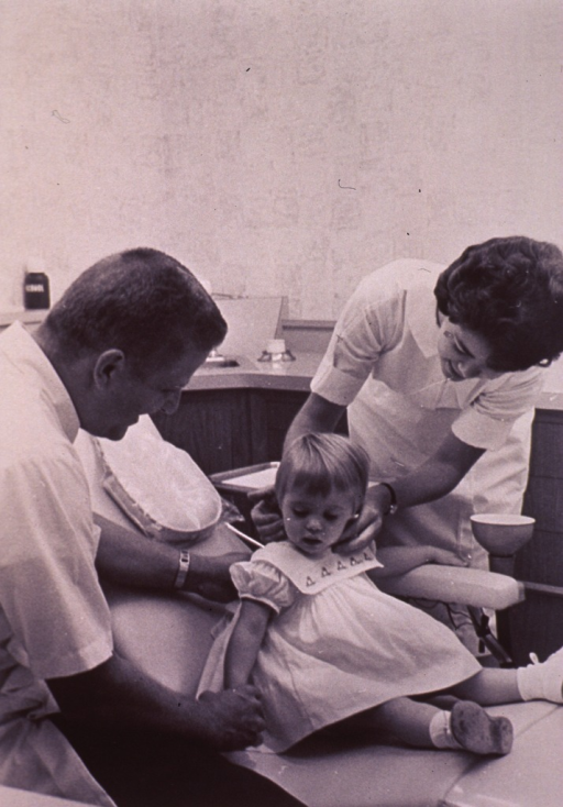 <p>A little girl is sitting in a dental chair; a dentist and his assistant are on opposite sides of the chair.</p>