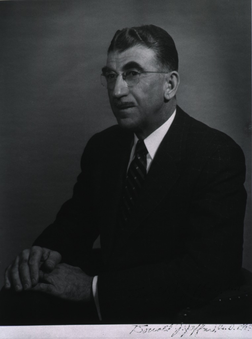 <p>Half-length, seated, left pose; wearing glasses; hands clasped on knee.</p>