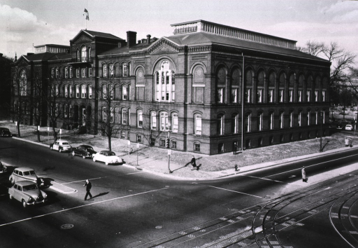 <p>Exterior view: cars are parked in front of the Army Medical Museum and Library building; a man is crossing the street, another man is standing in the street, people are on the sidewalk; trolley tracks are in the foreground.</p>