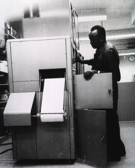 <p>Interior view: Mr. Shifflett makes adjustments to the machine printing from microfilm on to paper.</p>