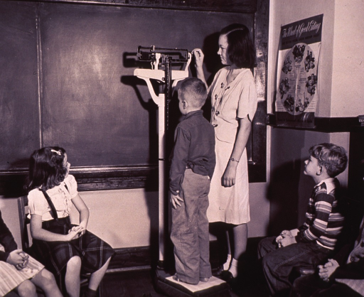 <p>Interior view of a school classroom: a child standing on a scale is having his height and weight measured; other children are waiting.</p>