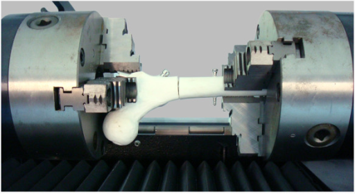 torsion tester. femoral model within the torsion testing machine. photograph demonstrating a placed horizontally in tester