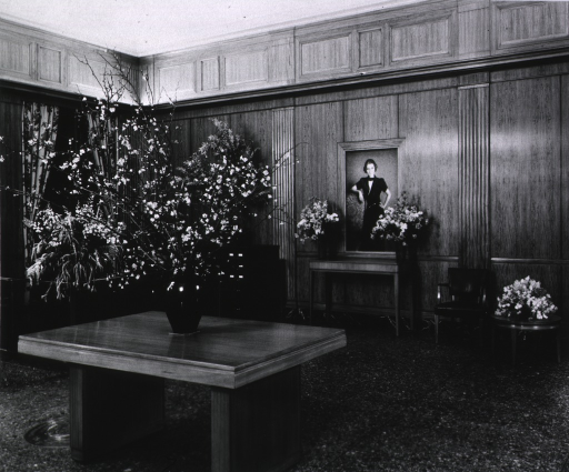 <p>Interior view of ornately paneled room with several tables and floral arrangements, and a three-quarter length portrait of a woman.</p>