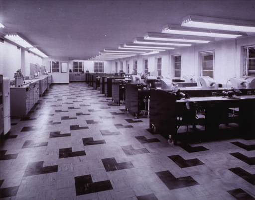 <p>Interior view: ten rows of tables with suction devices are by the windows. The work tables are two-sided.   A refridgerator and counters with equipment line the opposite wall.</p>