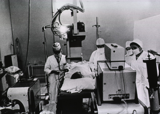 <p>Interior of an examination room; two physicians and two nurses observe as a patient is given an angiogram.</p>