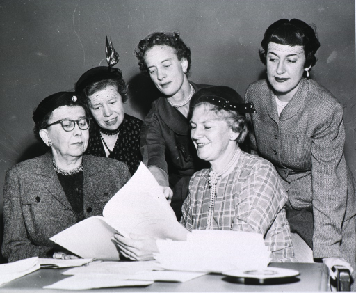 <p>View of five members of the board looking at documents on a table.</p>