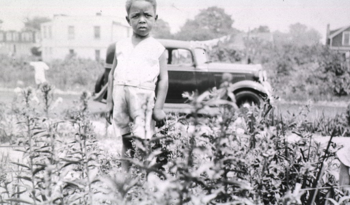 <p>View of the child who is standing in a field.  A car and house are in the background.</p>