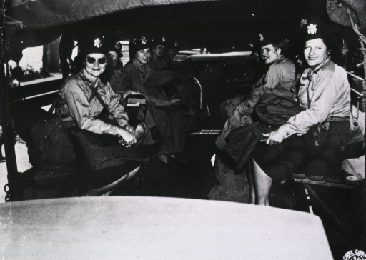 <p>Subect:  A group of female military nurses sits on benches on the tarp-covered bed of a military vehicle.</p>