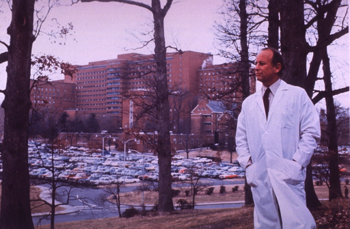 <p>Dr. Donald S. Fredrickson is standing in front of a tree on a hill with his hands in the pockets of his lab coat.  A parking lot is between Dr. Fredrickson and the Clinical Center.</p>