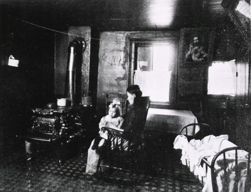 <p>Interior view: cast-iron stove, crib, picture of Jesus, table with cloth; woman is sitting in a rocking chair with a child on her lap.</p>
