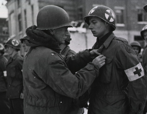 <p>Servicemen stand at attention in a row in front of a building.  It is daytime, and snow covers the ground.  Brigadier General Perrin pins the medal on the jacket of one of the servicemen.</p>