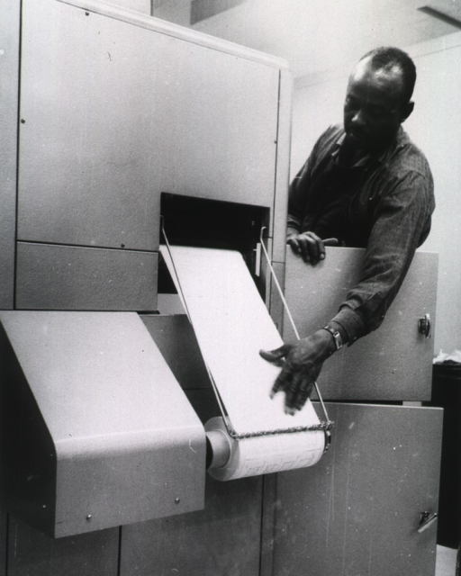 <p>Interior view: Mr. Shifflett at copy flo machine as it prints from microfilm on to paper.</p>
