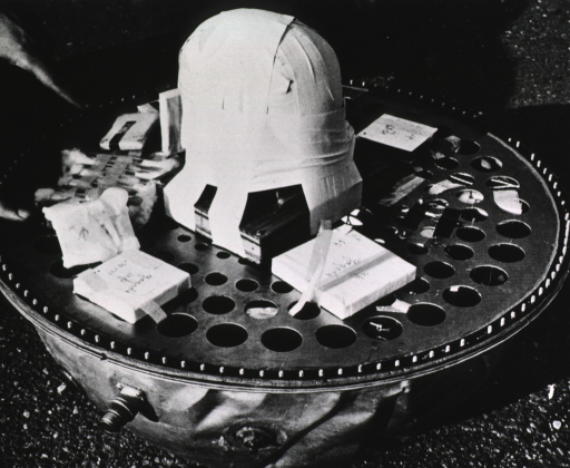 <p>A metal tub-like recording device with a simulated skull (a mass of tape shaped like a skull) in the center; sensitized plates are attached to the device around the 'skull.'</p>