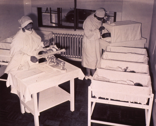 <p>One African American nurse is weighing an infant; the other is looking in on the infant the heated crib.</p>