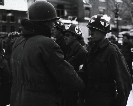 <p>Servicemen stand at attention in a row in front of a building.  It is daytime, and snow covers the ground.  Brigadier General Perrin shakes the hand of one of the servicemen.</p>