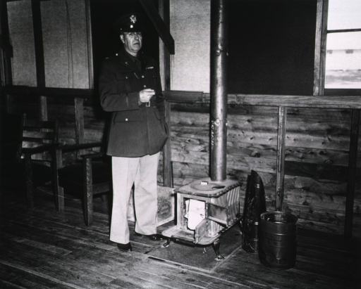 <p>An unidentified serviceman in uniform poses next to a stove.</p>