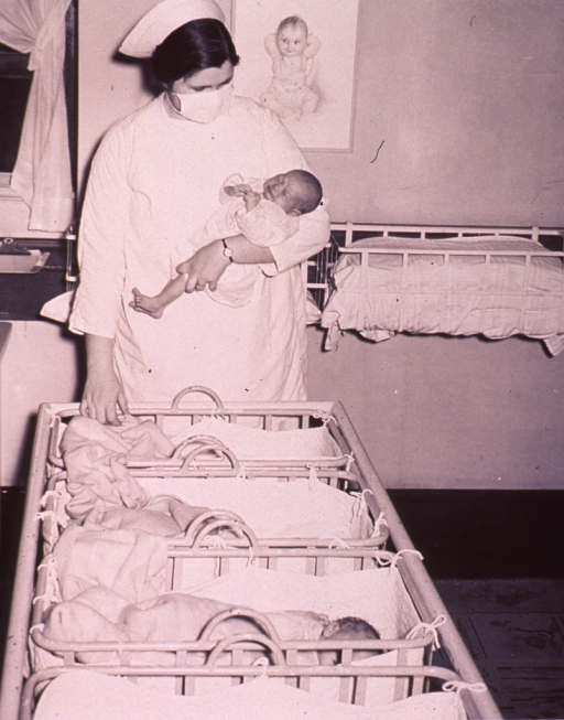 <p>A nurse is holding an infant in a nursery.</p>