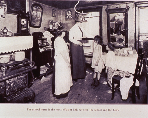 <p>Interior view: a woman is examining two young children in the dining area of the home; a woman (the mother) is standing to the left; further to the left is a large stove situated next to a fireplace.</p>