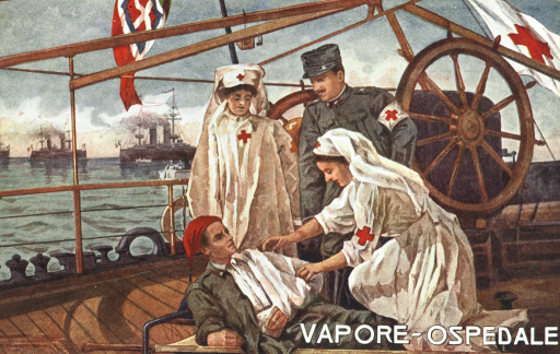 <p>On board a war ship, an injured officer on a stretcher is cared for by a nurse in white uniform with a red cross on the sleeve and hat.  Another nurse and an officer are standing behind them observing.  In the background the Red Cross flag is flying in the air and there are other war ships in the distance.</p>