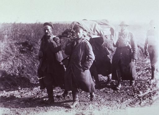 <p>Showing a German prisoner helping American Red Cross workers transporting wounded on the road leading into Riqueval, near Bellecourt, France.</p>