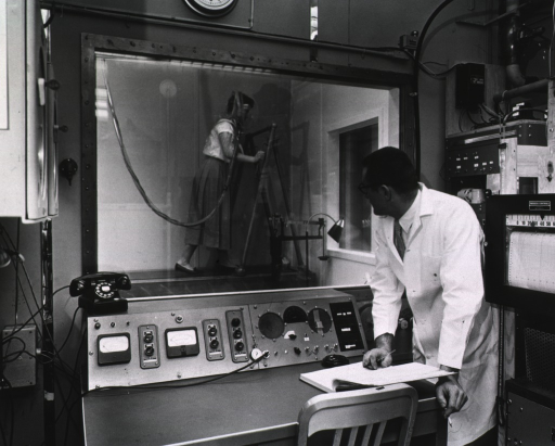 <p>A woman exercising on a treadmill in a metabolic chamber; in the foreground a man monitors her energy expenditure.</p>