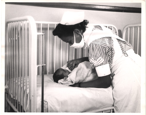 <p>A nurse is leaning over a newborn in a crib.</p>