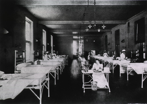 <p>Interior view of the woman's surgical ward at the Presbyterian Hospital in New York; beds line the walls on both sides of the room, and there are tables, or nurse stations, in the center isle.</p>