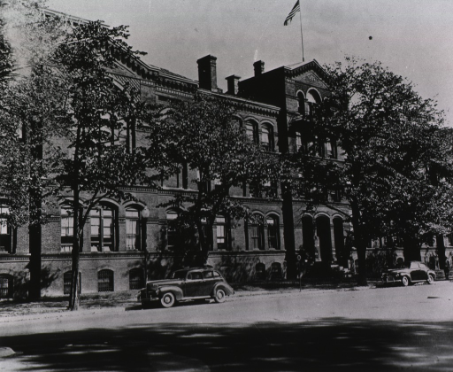 <p>Exterior view of the Army Medical Museum and Library building: front facade partially hidden by trees; two automobiles parked in the street.</p>