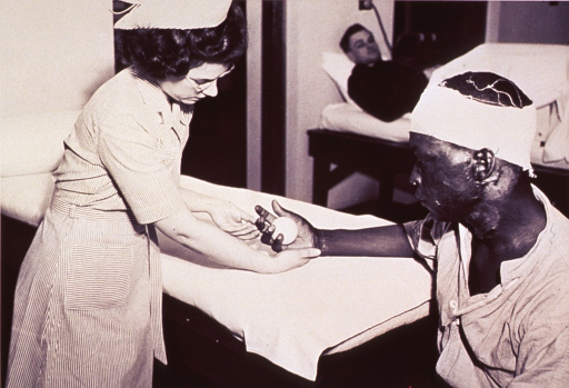 <p>A physical therapist gives hand exercises to a patient who has received burns.  A tennis ball rests in the patient's right hand palm, his right forearm resting on a bed or padded table, while the physical therapist helps the patient close his fingers.  The patient's head has burns and there is a white bandage around his head.  There is another patient lying in bed in the background with what appears to be a tent over the lower part of his body.</p>