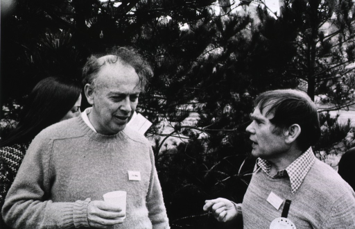 <p>Dr. James Watson (left, standing) talking with  Dr. Sydney Brenner (right, standing) at the Asilomar Conference, Pacific Grove, California, February 24-27, 1975.</p>