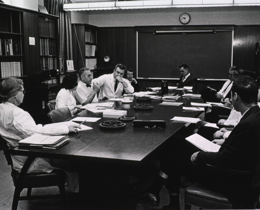 <p>Men and women are seated around a conference table.</p>