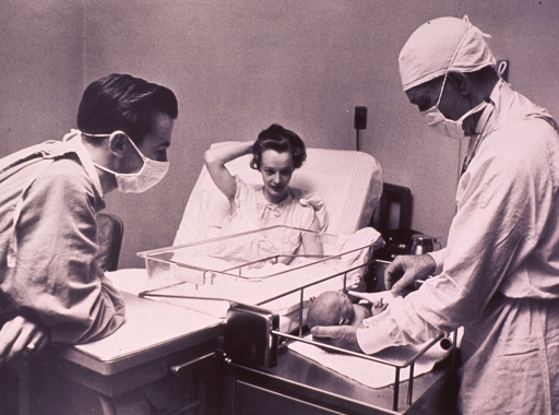 <p>The proud parents observe as a physician examines the newborn at the mother's bedside.</p>