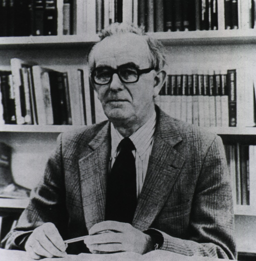 <p>Seated behind desk holding a pencil with bookshelves behind him.</p>