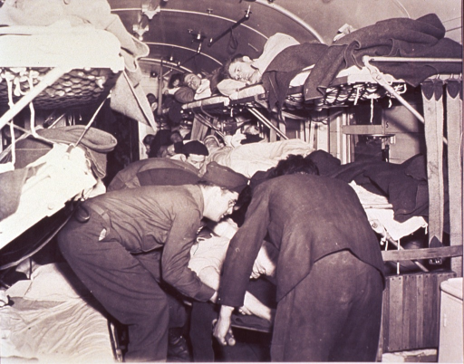 <p>Patient being loaded by five men onto a stretcher from a bed on a hospital train car.  There are two rows of bunk-style beds on either side of the train car with a patient in each bed.  Some of the patients are watching the transfer while others have their eyes closed.  According to the photo caption, the train is the Gare St. Lazare hospital train.</p>