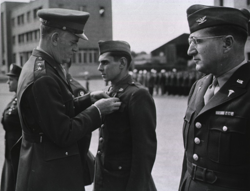 <p>Servicemen stand at attention in a row on a plaza in front of a building.  General Hughes pins the medal on the jacket of Pvt. Greenberg.</p>