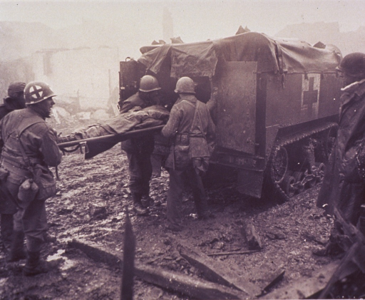 <p>A wounded soldier lying on a stretcher is being loaded into a medic half-track.  There is a red cross painted on the side of the vehicle.  Another soldier looks on.  One of the four soldiers holding the stretcher has a red cross painted on his helmet.   The ground is muddy and there are ruined buildings in the background.  According to photo caption, the picture was taken in Echtz, Germany.</p>