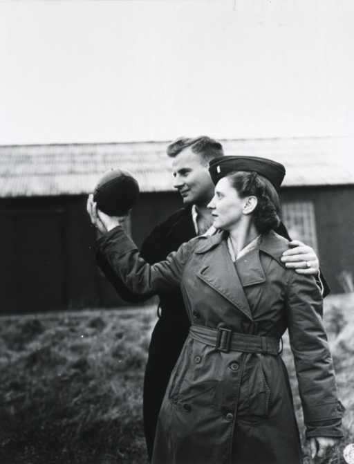 <p>Sgt. Joe Laiber, patient, teaching Keefe how to throw a football.  Outdoor scene, both shown three-quarter length; Keefe wearing overcoat and cap; building in background.</p>